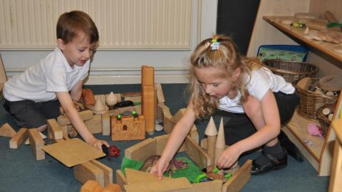 Children playing with small world toys in EYFS.